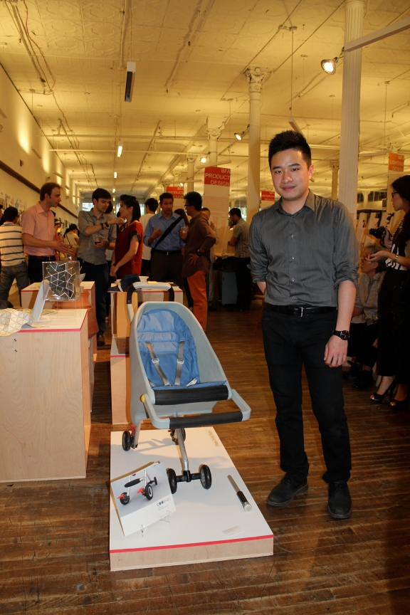 """Daulton Kao posing with his Senior Thesis project """"Coo-Baby"""" during the exhibition"""